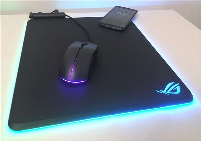 Mouse pad-ul ASUS ROG Balteus Qi mouse încărcând un smartphone