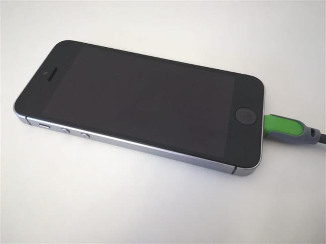 Un iPhone SE conectat la PC cu un cablu Lightning
