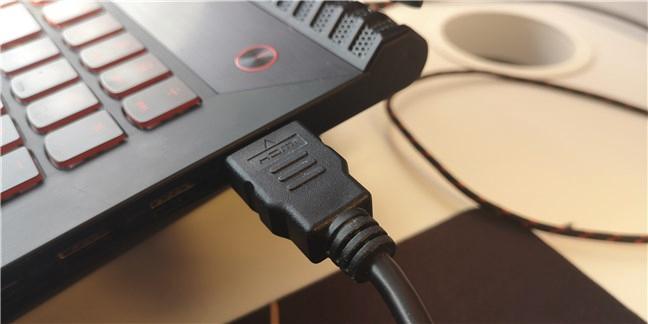 Un cablu HDMI conectat la portul HDMI de pe un laptop