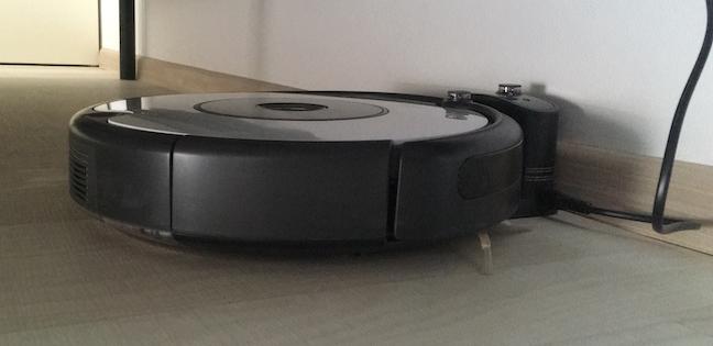 Roomba andocat în siguranță în baza lui de încărcare de sub pat