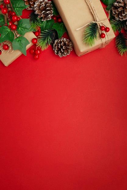 Cadouri de Crăciun și decorațiuni peste un fundal roșu
